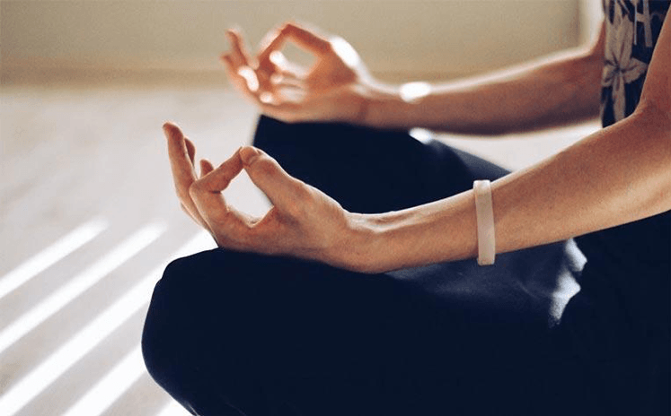 woman meditating to relieve caregiver stress