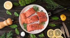 salmon-fillet-on-rustic-kitchen-table-with-fresh-ingredients-for-tasty-cooking-and-frying-pan_t20_wq2dpk
