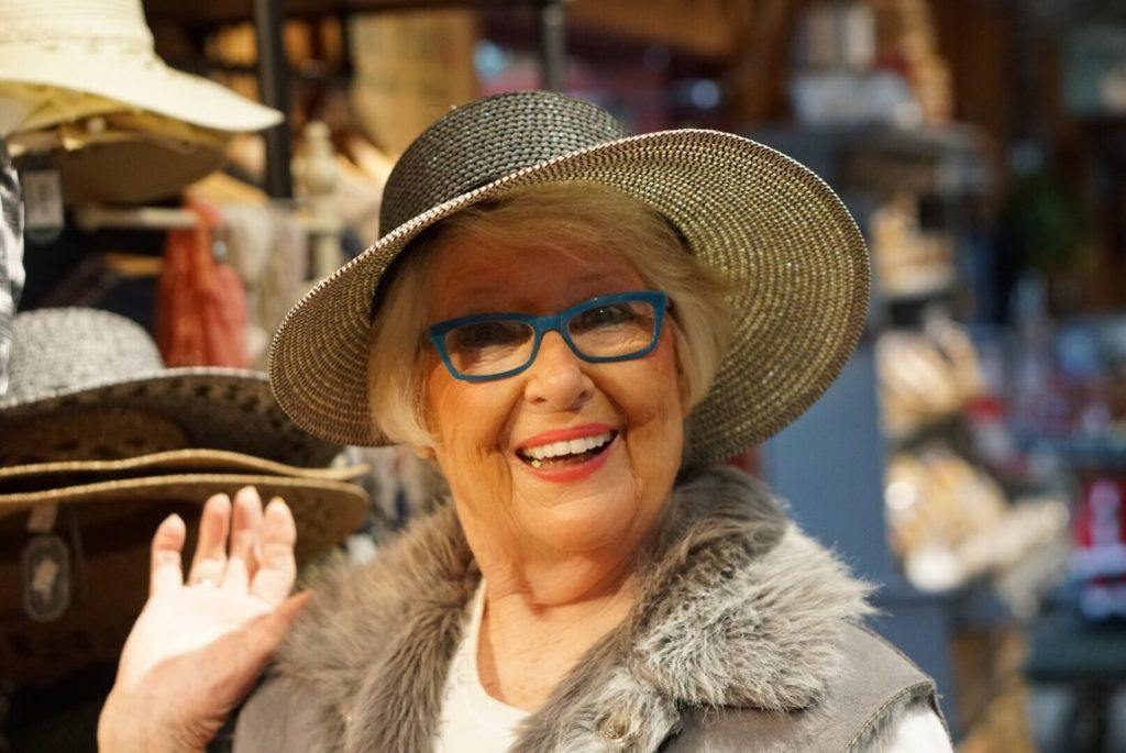Photo: A woman is smiling and waving while trying on a hat. She has blue glasses and a bright, energetic smile.