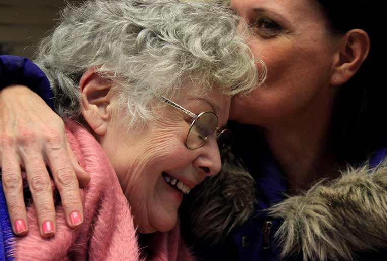 Photo: Adult woman hugging mom and kissing her on the head
