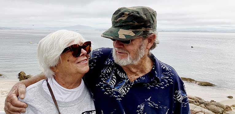 older couple hugging at the beach