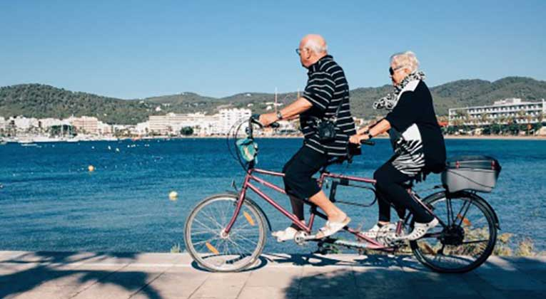 Photo: older couple riding a tandem bike by water
