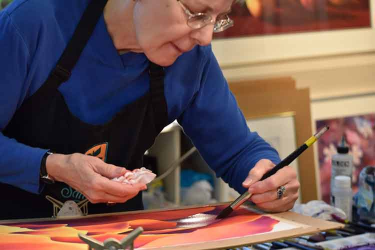 Photo: Older woman painting