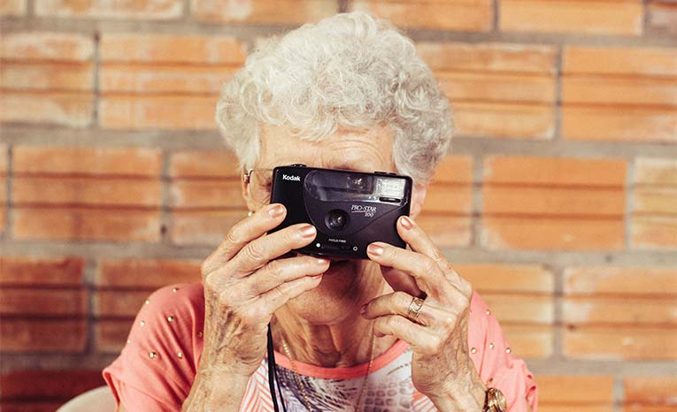 older woman with camera in front of face