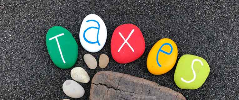 colorful rocks spelling the word taxes