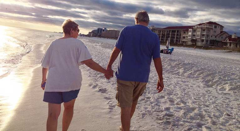 older couple holding hands on the beach