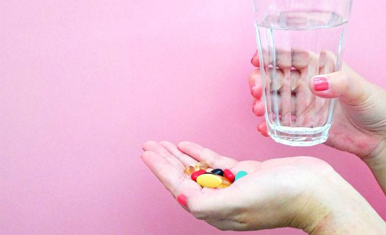 colorful pills in one hand and water in the other
