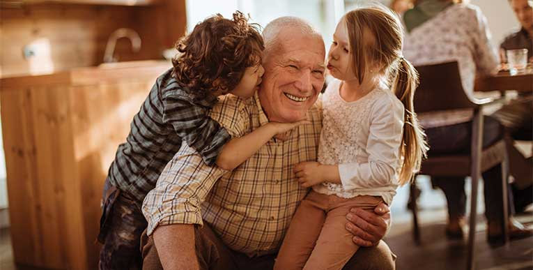 grandfather playing with grandson and granddaughter