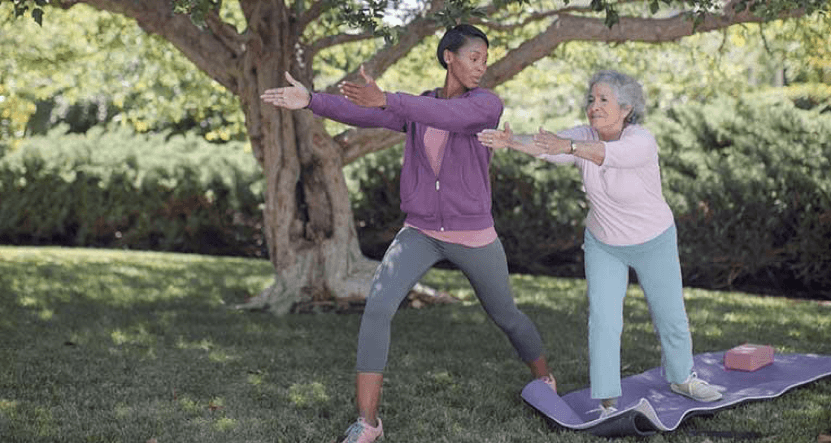 older woman doing yoga with caregiver