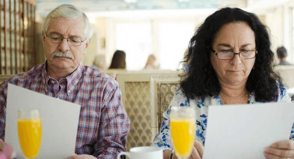 couple looking over paperwork with mimosas