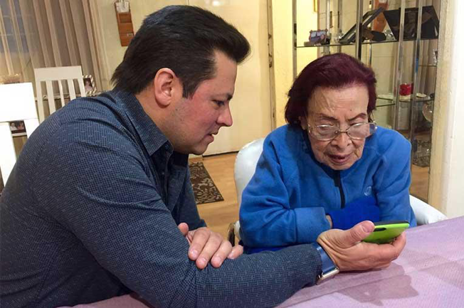 adult son helping mother with phone