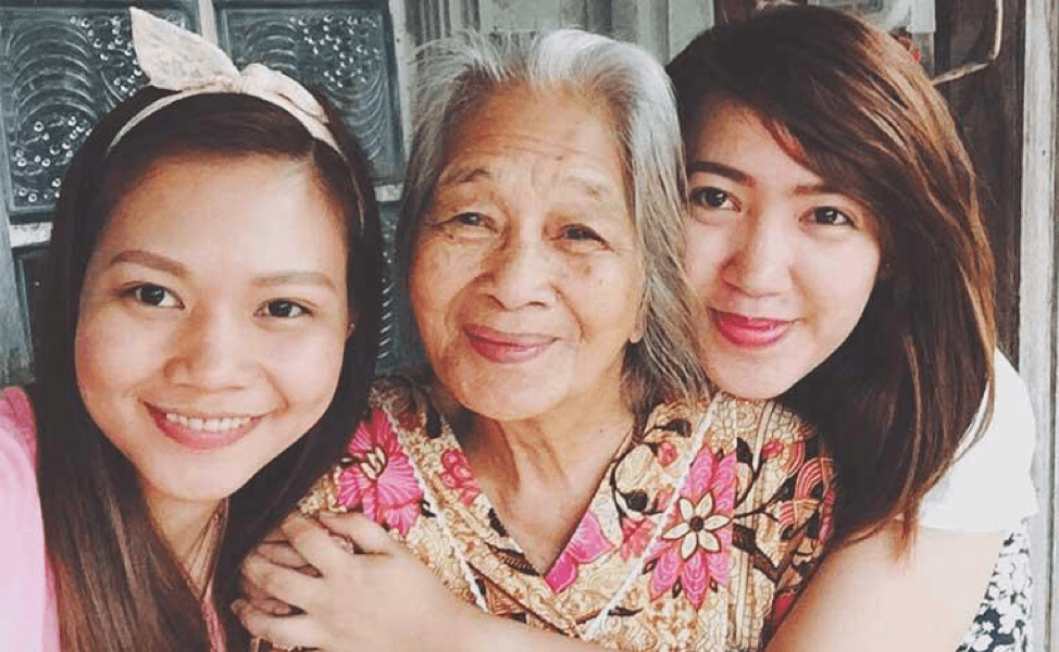 grandmother with thwo granddaughters smiling at camera