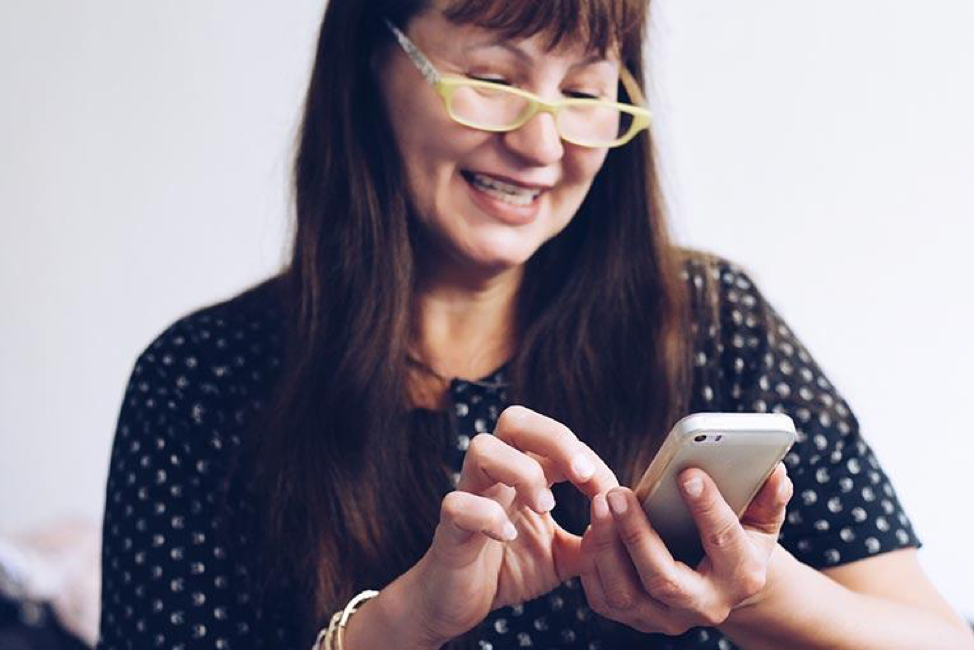 woman smiling and using cell phone